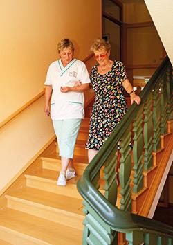 Pflegerin hilft einer Seniorin die Treppe hinab
